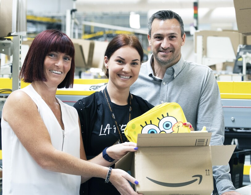 Karen and Chris from Character.com pictuerd smiling at the camera with Amazon employee, Donata - who is putting a SpongeBob SquarePants backpack (one of the sellers' items) into an Amazon box.