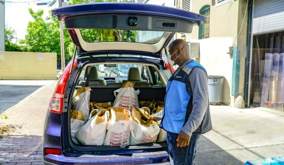 A delivery driver wearing a mask and an Amazon vest loads donations from a food pantry into his vehicle.