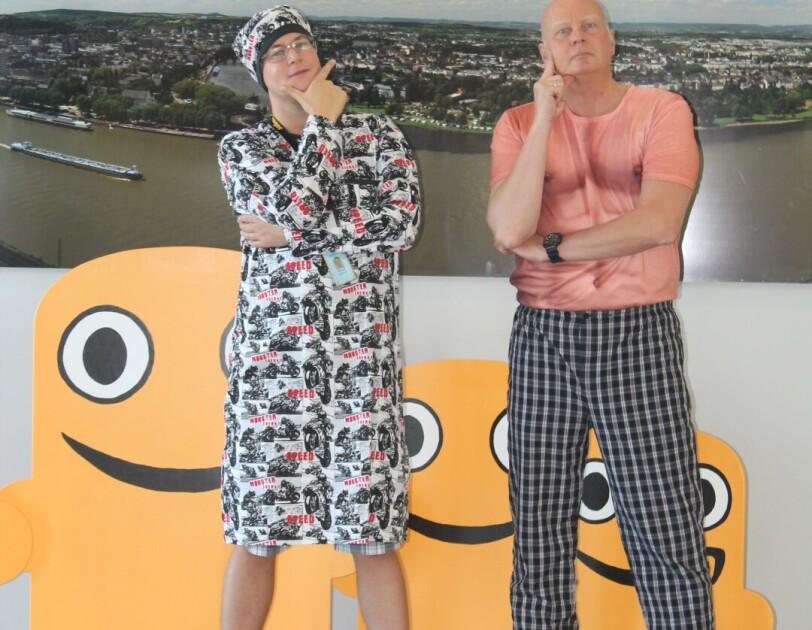 Zwei Mitarbeiter sind vor einer Fotorückwand zu sehen: Einer der beiden trägt ein Nachthemd mit passender Schlafmütze, der andere eine karierte Pyjama-Hose mit einem Shirt, auf dem eine männliche Bodybuilder-Brust zu sehen ist