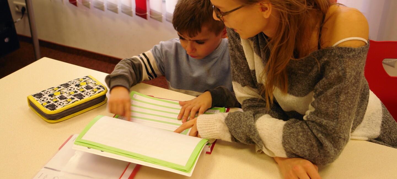 Ein kleiner Junge und eine junge Frau sitzen gemeinsam an einem Tisch und schauen auf ein Schulheft.