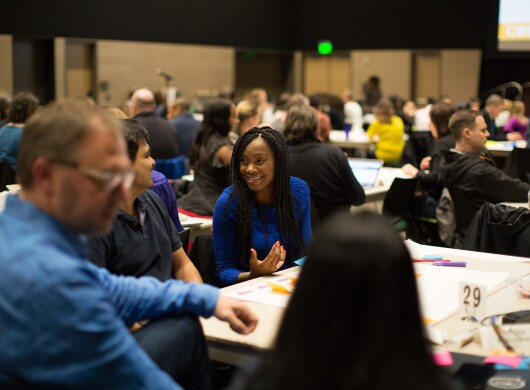 A woman in a blue sweater speaks to fellow conference attendees.
