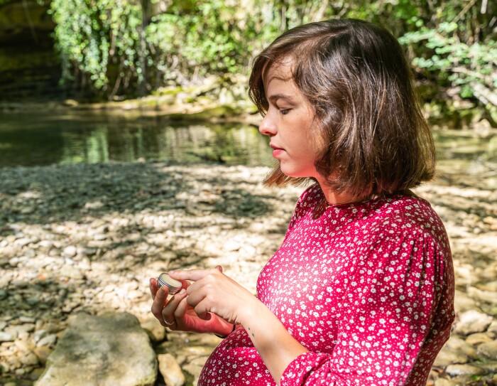 María Gómez Iribarnegaray con el  bálsamo labial de La cosmética de María.  María esñta embarazada y lleva un vestido rosa y  blanco de manga larga y cuello redondo. De fondo un río con piedras y verde.  En la mano tiene el recipiente del bálsamos y un anillo.