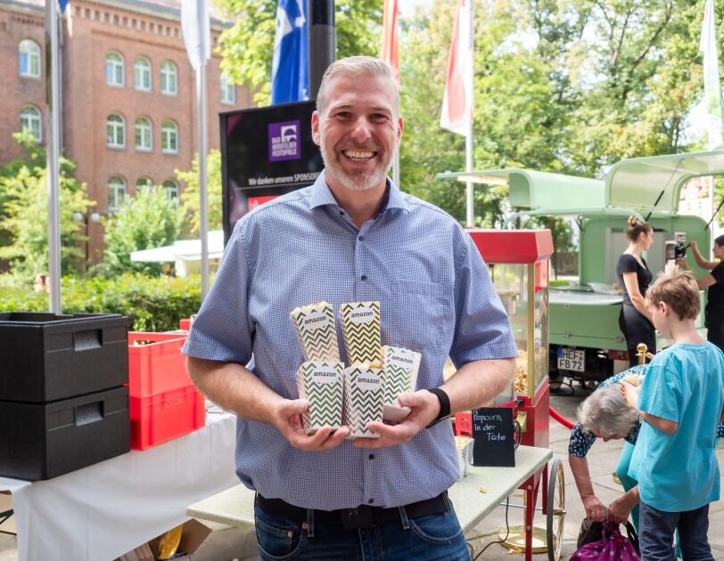 Ein Mann in Jeans und blauem Kurzarmhemd hält Popcorn-Tüten mit Amazon Aufdruck in der Hand.