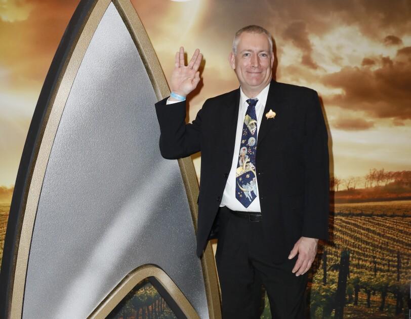 Ein Herr im dunklem Anzug steht rechts neben einem lebensgroßen Star Trek Logo.