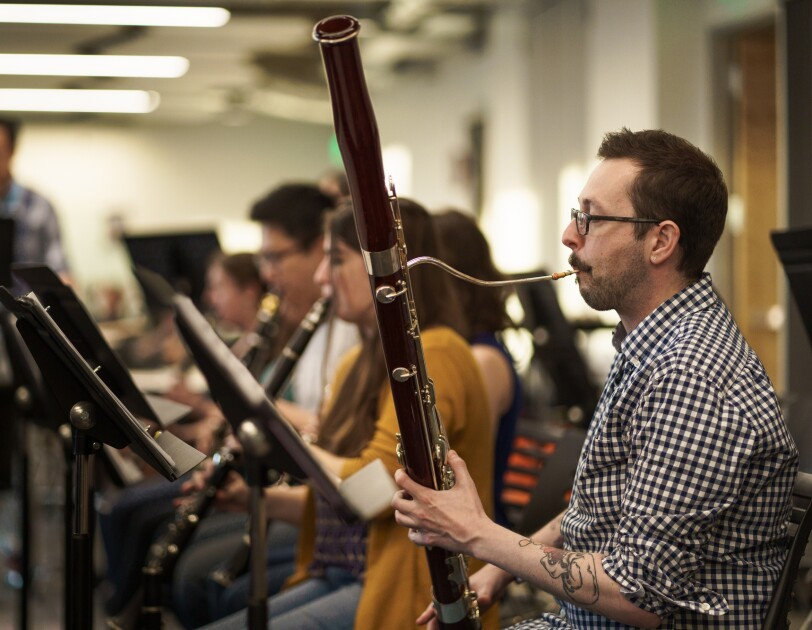 Na pierwszym planie mężczyzna grający na fagocie. W tle inni członkowie orkiestry