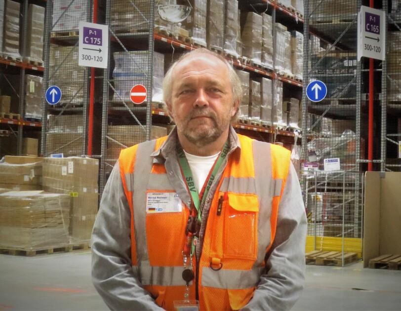 Oberkörperprofil eines Amazon Mitarbeiters in orange-farbener Sicherheitsweste. Er steht vor einem Hochregallager.