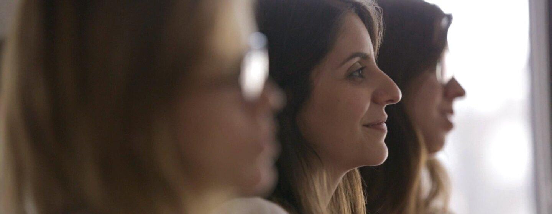 Tres mujeres de perfil y solo la del centro está enfocada. Tiene el pelo largo y observa enfrente sonriendo.