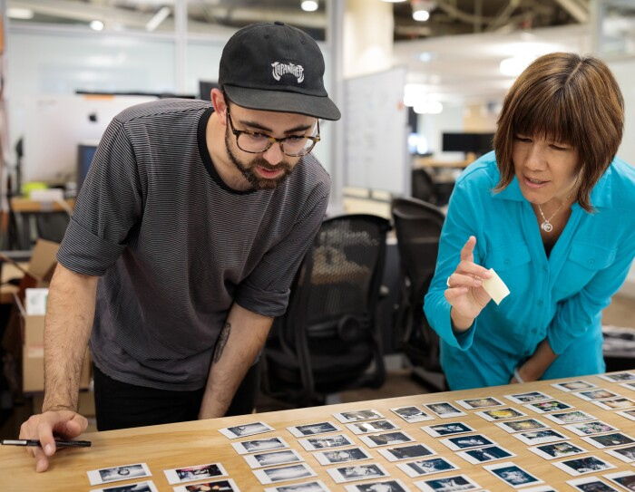 A man in a baseball cap and a woman in a teal blue top lean over a desk in an office setting. On the desk are dozens of small photographic prints. The woman holds a sticky note in her hand and prepares to point at an image.