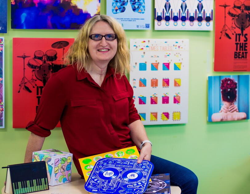 A blonde woman wearing glasses, jeans, and red button up shirt is seated on a tabletop in a room painted green, with myriad artwork hung on the wall.