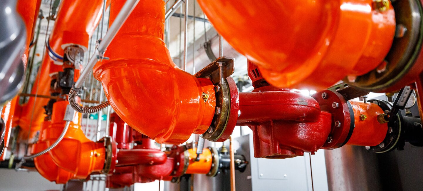 Three bright orange steam pipes are seen in a mechanical room under the Westin hotel in Seattle.