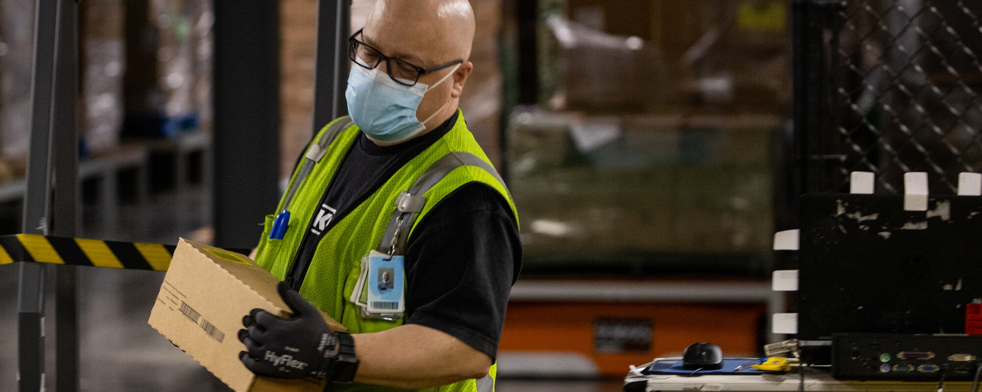 A man wearing gloves, a mask, and a safety vest carries a small box.