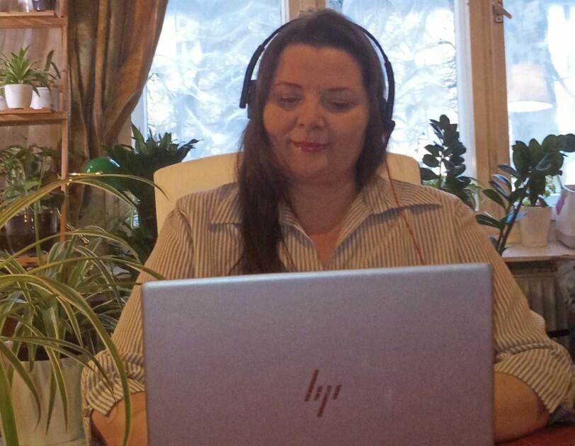 Eine Frau mit Kopfhörern sitzt an einem Tisch und schaut in ihren Laptop.