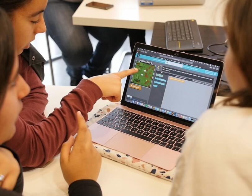 Trois jeunes filles réalisent ensembles un exercice de code sur un ordinateur.