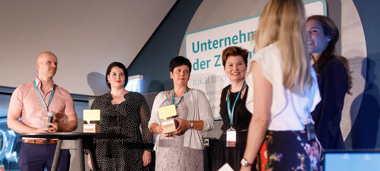 Die Gewinnerinnen von Unternehmerinnen der Zukunft stehen auf der Bühne und freuen sich über den Pokal. Im Hintergrund sieht man das UdZ Logo.