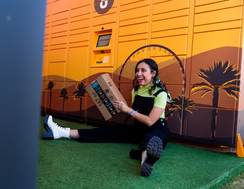 A seated woman leans against a bank of lockers. She's smiling and holds an Amazon box.