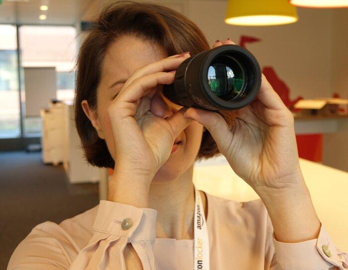 Una donna in un ufficio guarda verso l'orizzonte attraverso un monocolo. Regge lo strumento con due mani.