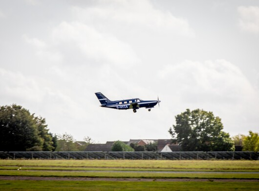 A small plane taking flight above a runway.