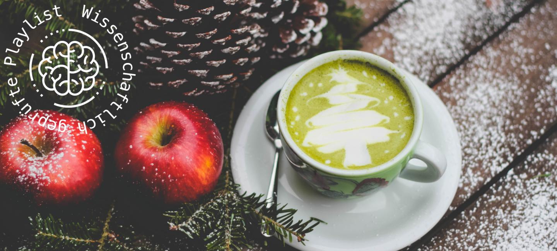 Auf einem Tisch steht eine Tasse mit Kaffee. Ihr Milchschaum hat die Form eines Tannenbaums. Neben der Tasse liegen zwei Äpfel und Tannenzapfen.