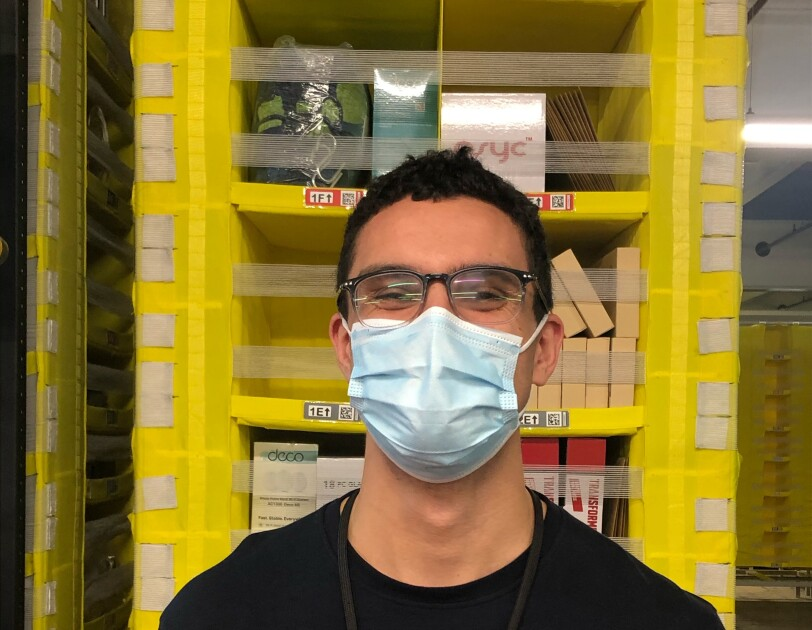 Lorcan Keating, an associate at Amazon's fulfilment centre in Durham, pictured at his work station with shelving pods in the background. He is smiling at the camera and wearing a face mask.