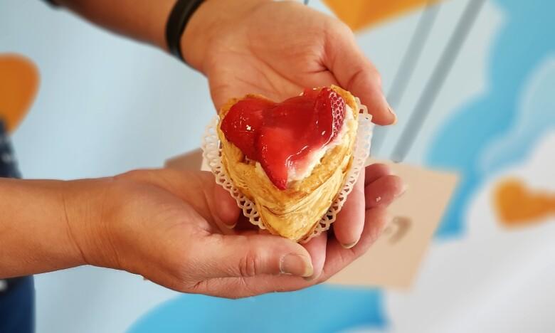 Ein kleiner Kuchen in Herzform in Nahaufnahme, man sieht die Hände, die den Kuchen halten