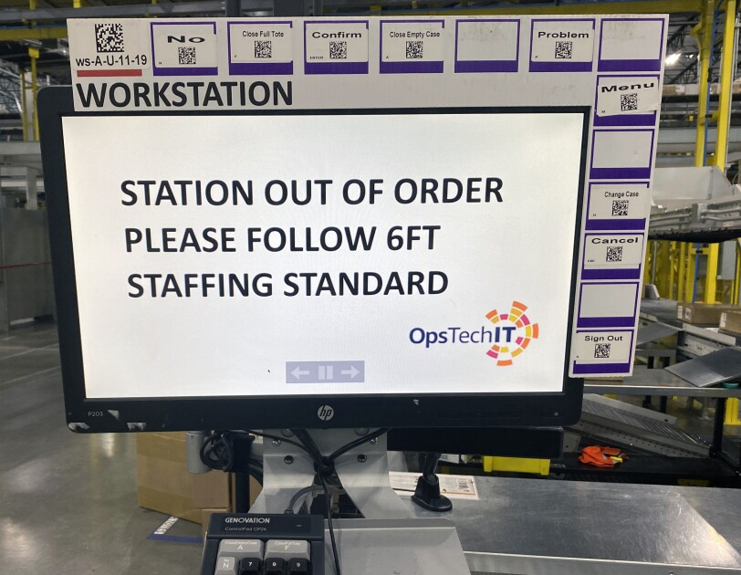 "Monitor at a workstation at an Amazon fulfillment center. The screen says ""station out of order, please follow 6ft staffing standard."""