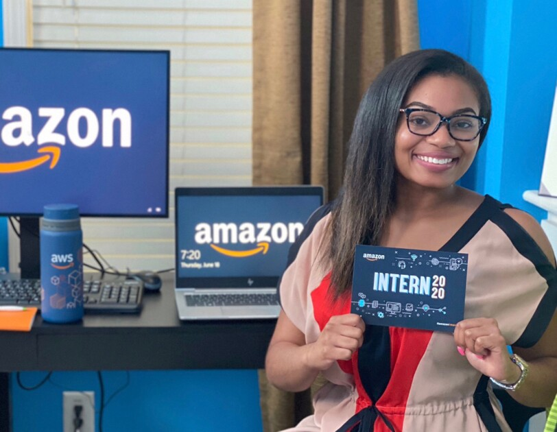 "A woman sits in front of a desk. She holds a card that says ""Amazon intern 2020."""