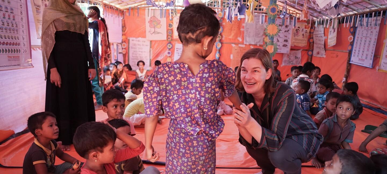 Ein Zelt mit vielen kleinen Kindern. Im Vordergrund spricht eine Frau der Organisation mit einem kleinen Mädchen im Blumenkleid. Sie hält dabei ihre Hand und lächelt sie an.