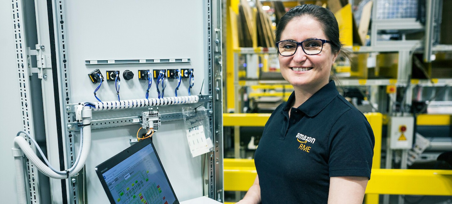 Apprentice, Carla Bernadino, pictured working on her laptop and smiling at the camera with warehouse machinery in the background.