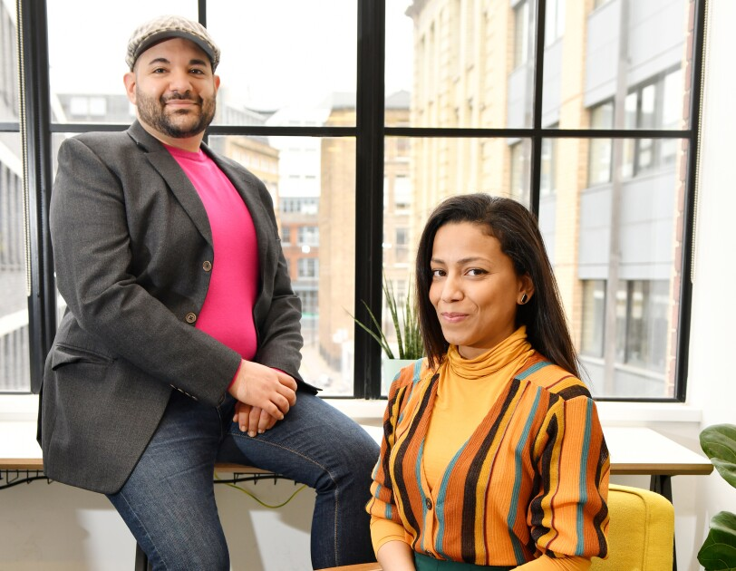 A portrait of Naveed and Samiya Parvez. Naveed is leaning against a window in their Shoreditch office, and Samiya is sitting on a rocking chair.