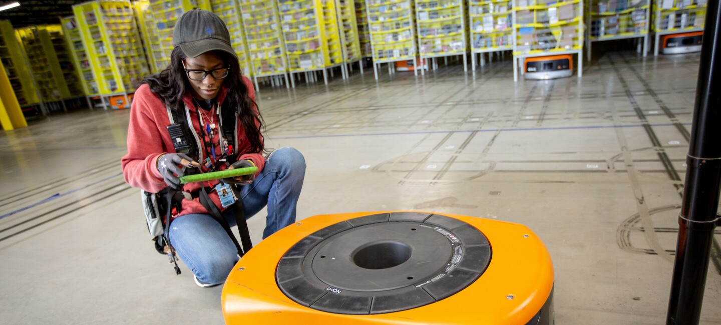 Amazon Robotics technician attends to a fulfillment center robot