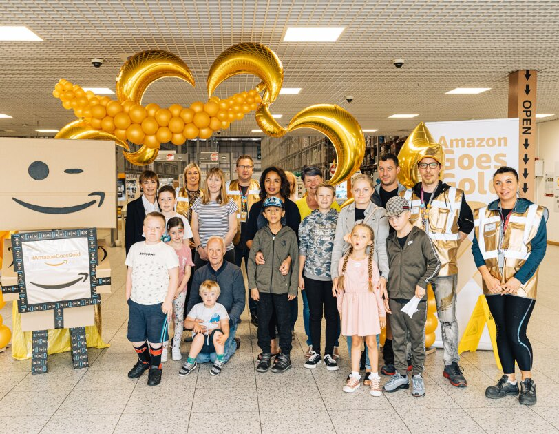 Amazon Goes Gold: golden decorations, children and Amazon employees with golden vests inside an Amazon fulfilment centre