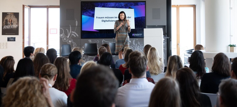 """Ein gemischtes Publikum lauscht gespannt einem Vortrag zum Thema """"Frauen und Digitalisierung""""."""