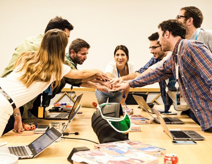El equipo que ha estado preparando Prime Day se encuenta en la war room  celebrando el inicio de un intenso día. Siete jóvenes amazonians juntan las manos en el centro de la mesa. Una mesa que está llena de ordenadores y cajas de pizzas.