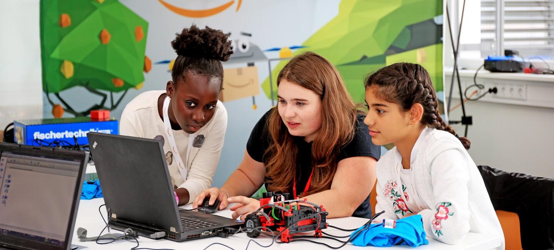 Eine Trainerin sitzt am Rechner, neben ihr zwei  ca. 12-jährigen Mädchen