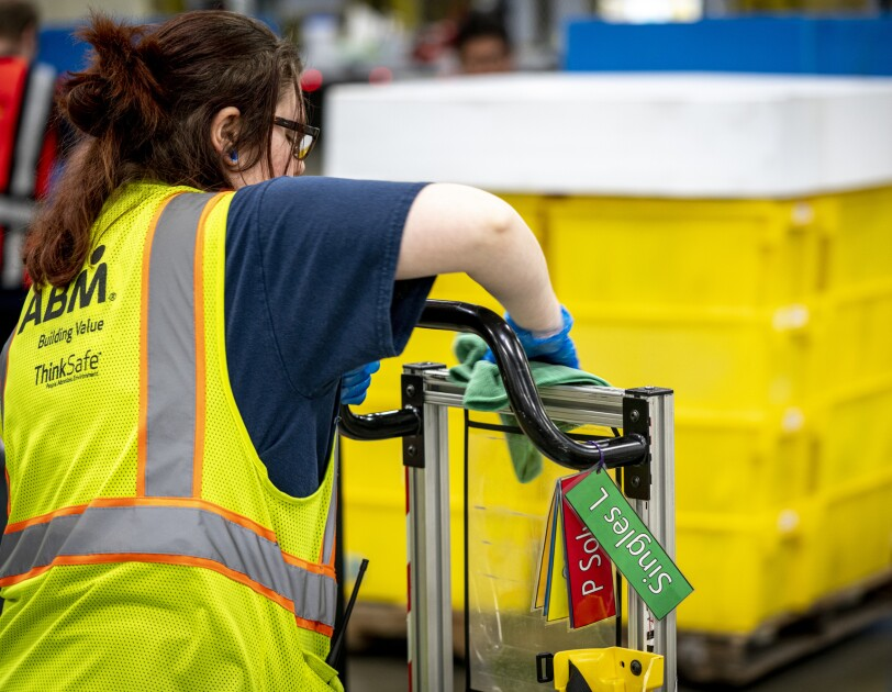 A woman wipes down a piece of machinery at an Amazon fulfillment center.