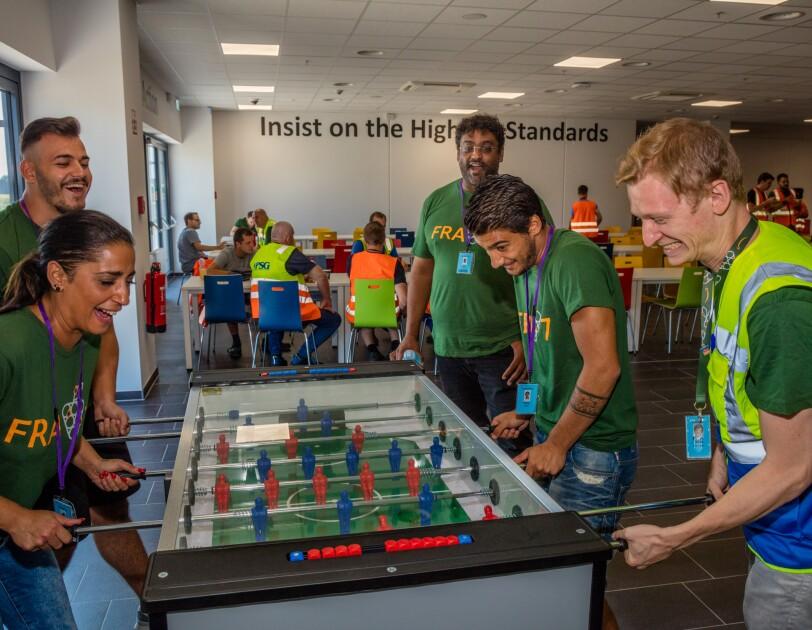 Vier Mitarbeiter spielen Kicker. Auf ihren Gesichtern Lachen und Freude. Ein fünfter Mitarbeiter beobachtet lächelnd seine Kollegen.
