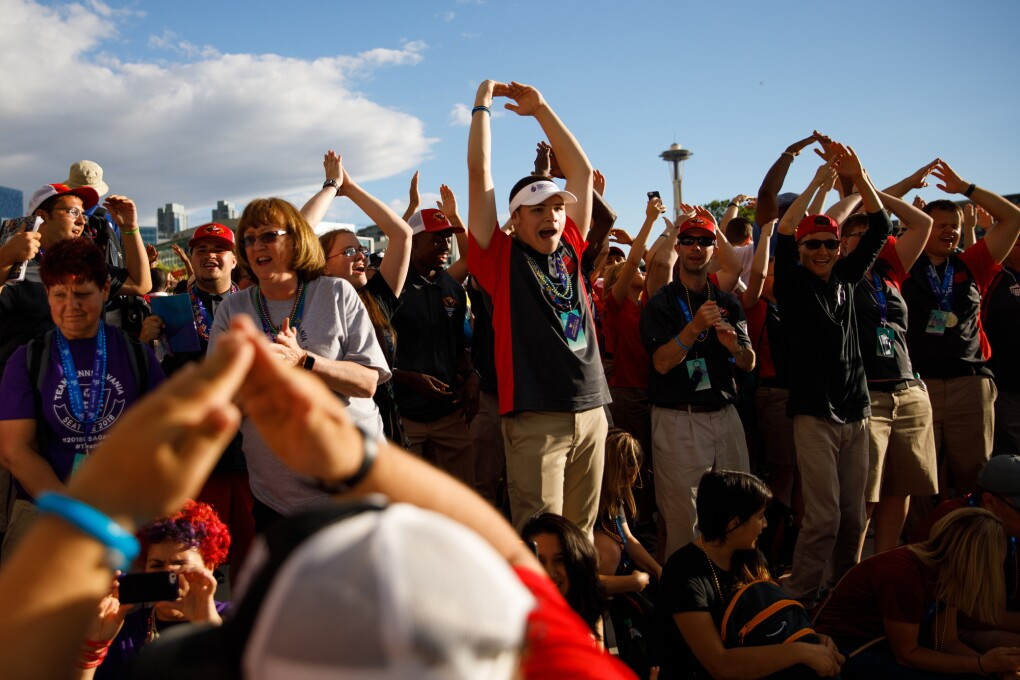 2018 Special Olympics USA Games athletes cheer at the closing ceremony. Many of the atheletes are seen holding their arms up, above the head, with fingers touching. Other individuals are clapping.
