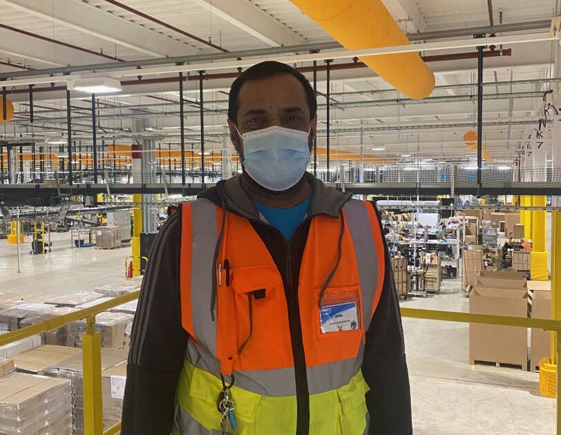 Imtiaz Hussain, stores coordinator, standing in a fulfilment centre wearing a high-vis jacket.