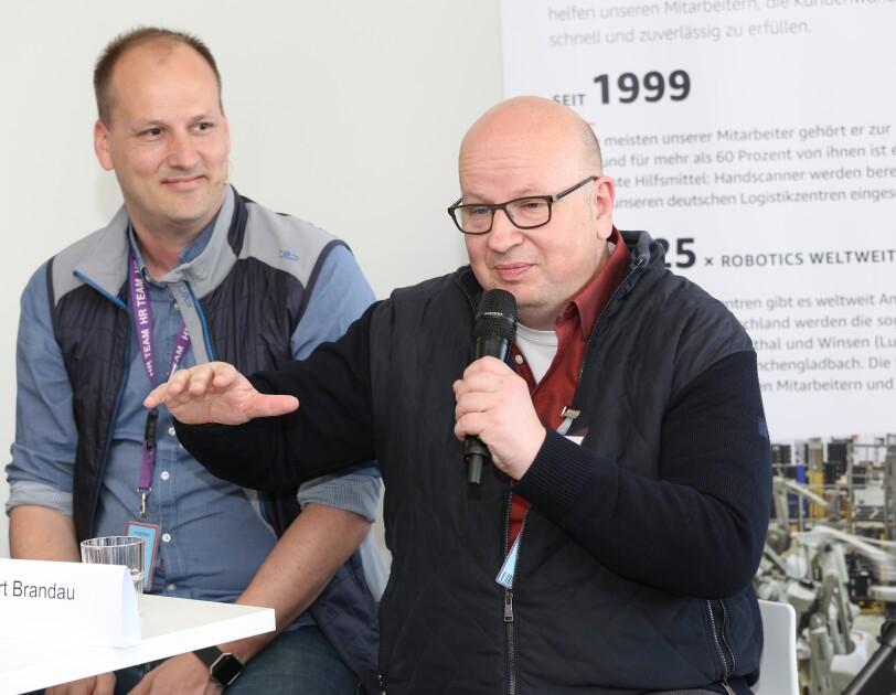 Robert Marhan blickt zu Norbert Brandau, der ins MIkrofon spricht