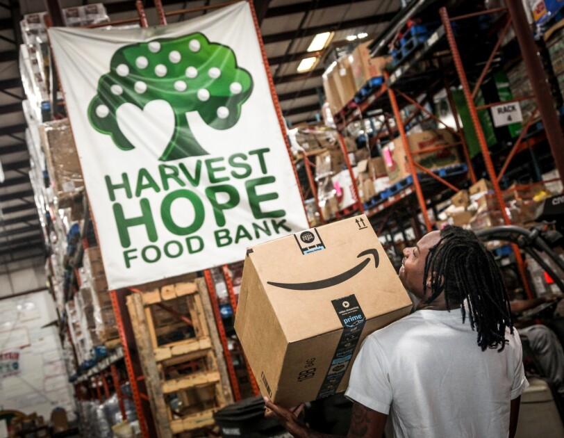 "A man walks through a warehouse space under a banner marked ""Harvest Hope Food Bank."" He carries an Amazon box."