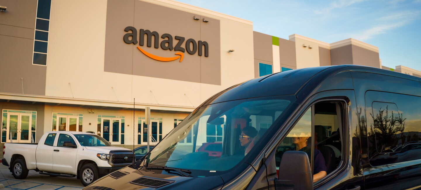 Une camionnette noire traverse un parking flanqué d'un bâtiment portant le logo Amazon