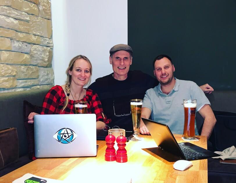 Zwei Männer und eine Frau lachen in die Kamera. Vor ihnen stehen Laptops auf einem Tisch.