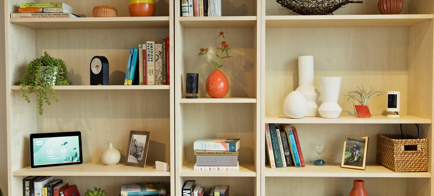 A bookshelf with books, decor, vases and baskets, clock, Echo Show, and Ring camera, illustrating a Smart Home setting.
