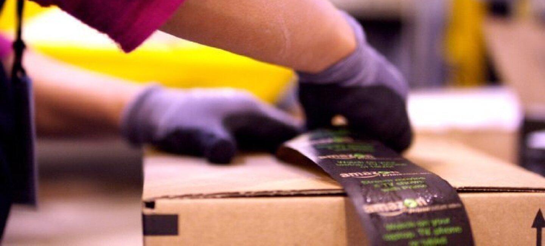 Dettaglio del momento in cui un pacco Amazon viene sigillato. In basso, l'apertura della scatola, mentre le mani dell'impiegato, con dei guanti, incollano il nastro Amazon.