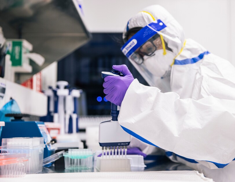 A person in PPE works in a lab.