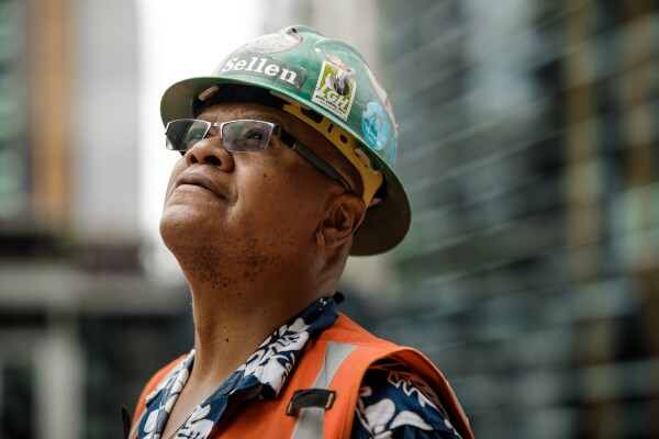 A man in a safety helmet and an orange safety vest stands outside, looking at buildings under construction.