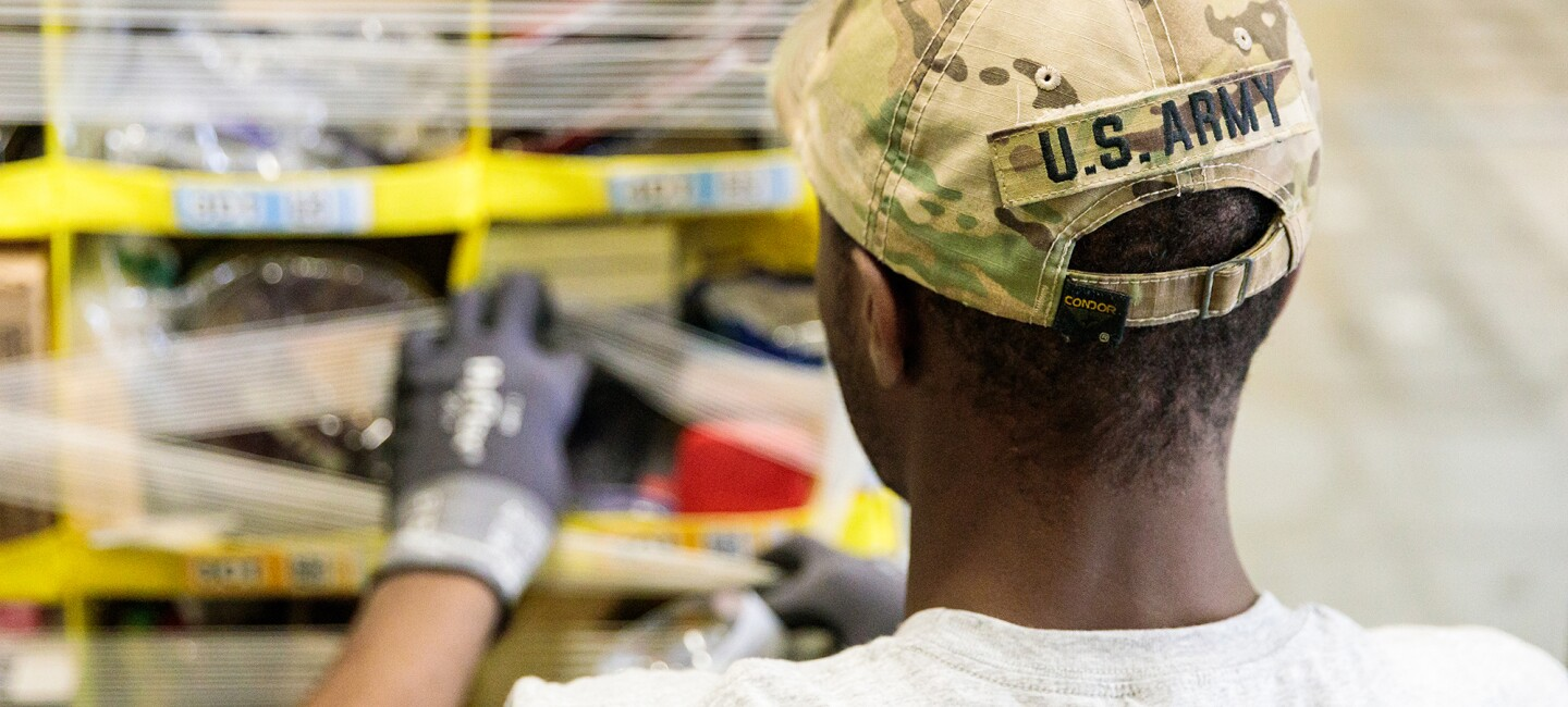 A man wearing a U.S. ARMY hat works in an Amazon fulfillment center.