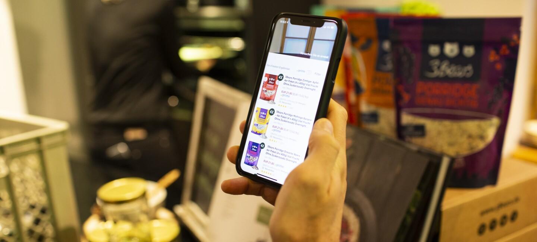 Ein Mann bestellt über die Amazon auf seinem Handy ein Produkt