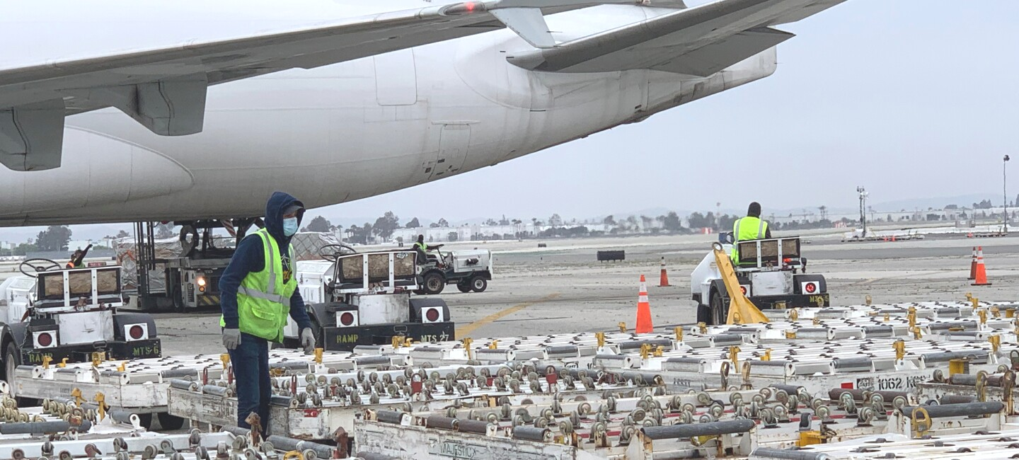 Airport ground crews unload a cargo plane.