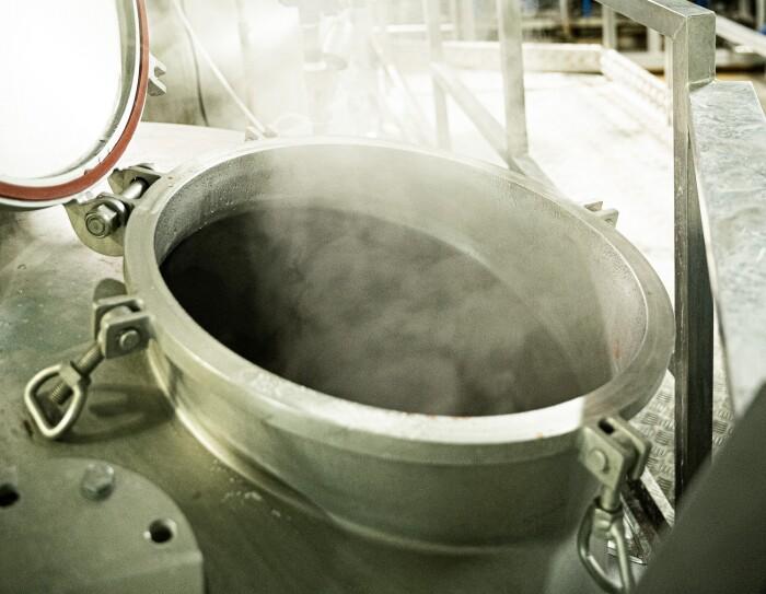 Primer plano de la producción de la salsa Espicy. En la fábrica hay un recipiente metálico del que sale humo.